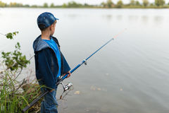 Child on a summer fishing on the shore. Attentive , focused, serious child is on a summer fishing on the river with a fishing rod in his hands Stock Image