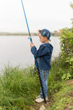 Child on a summer fishing on the shore Stock Photos