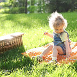 Child in summer park. Beautiful child sitting on grass in summer park stock photos