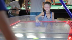 Child summer on vacation playing air hockey, joy