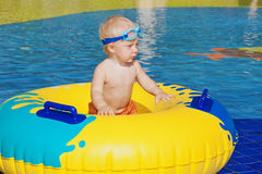 Child sunbathing, swim with inflatable toy in swimming pool. Happy family has a fun in beach pool - baby boy sunbathing, swim with inflatable toy. Healthy Royalty Free Stock Image