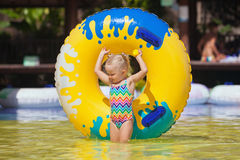 Child sunbathing, swim with inflatable toy in swimming pool. Happy family has a fun in beach pool - baby girl sunbathing, swim with inflatable toy. Healthy Stock Photo