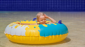 Child sunbathing, swim with inflatable toy in swimming pool. Happy family has a fun in beach pool - baby girl sunbathing, swim with inflatable toy. Healthy Stock Image