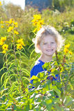 Child in sunflowers. A happy and smiling young blond girl standing in a garden of sunflowers on a bright and sunny day royalty free stock images