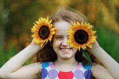Child with sunflowers in his hand show white teeth; enjoying nat. Ure in summer sunny day. Healthcare; freedom and happy childhood concept stock image