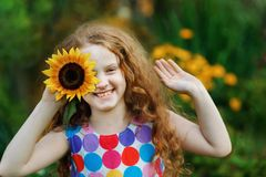 Child with sunflowers in his hand show white teeth, enjoying nat. Ure in spring sunny day. Healthcare, freedom and happy childhood concept stock photos
