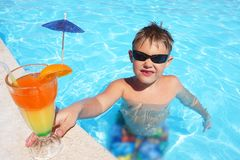 Child with colorful cocktail by the pool stock photos