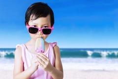 Child with sunglasses eats ice cream Stock Image