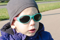 Child in sunglasses. Serious child in sea green color plastic sunglasses outdoors in warm purple jacket and a gray hat stock photo