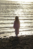 Child at sunset. A child thinks of what tomorrow might bring with the sun setting on the day Stock Photos
