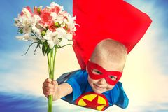 A child in a superhero costume with a bouquet of flowers flies to her beloved mother. The son in the costume of a superhero gives his mother a bouquet of stock images