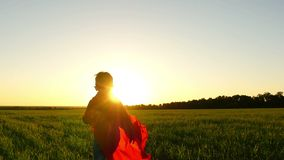 A child in a superhero costume in a red raincoat is running on a green lawn against the backdrop of a sunset simulating. A flight, at a slow pace. Slow motion stock video footage