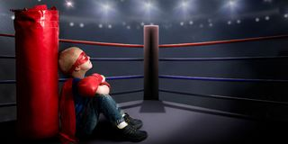 A child in a superhero costume sits in the ring and dreams of boxing victories. Children`s sports royalty free stock photography
