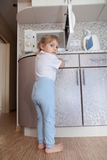 Child without supervision of parents playing with microwave stock photography