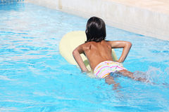 Child on surfboard. A tanned caucasian child on a surfboard in a swimmingpool Royalty Free Stock Photos