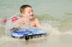 Child surfing on bodyboard at beach Stock Photography