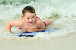 Child surfing on bodyboard at beach Royalty Free Stock Photo