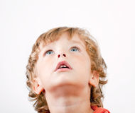 The child with surprise looks upwards. On a white background Stock Photo