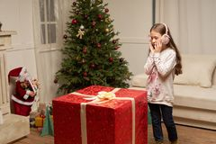 Child is surprised by big red gift for  new year Stock Photos