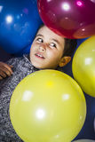 Child surrounded by balloons at a party Stock Image