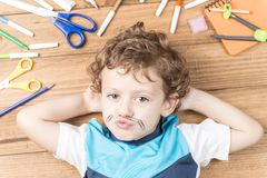 Child surrounded by school supplies. Concept back to school. Child lying on wooden boards, surrounded by school supplies and putting some clips like a mustache stock photography