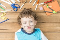 Child surrounded by school supplies. Concept back to school. Child lying on wooden boards, surrounded by school supplies and putting some clips like a mustache stock photo