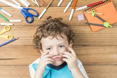 Child surrounded by school supplies. Concept back to school. Child lying on wooden boards, surrounded by school supplies and putting some clips like a mustache royalty free stock photography