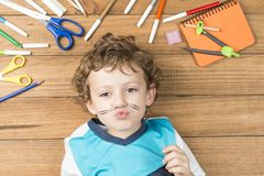 Child surrounded by school supplies. Concept back to school. Child lying on wooden boards, surrounded by school supplies and putting some clips like a mustache royalty free stock photo