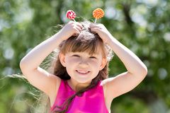 The girl is playing with big sweets on a stick. royalty free stock photos
