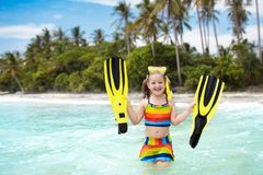 Child with swim fins snorkeling on tropical beach. Child with swim fins snorkeling on tropical ocean beach with palm trees. Little girl diving on exotic island Stock Image