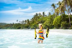 Child with swim fins snorkeling on tropical beach. Child with swim fins snorkeling on tropical ocean beach with palm trees. Little girl diving on exotic island Royalty Free Stock Image