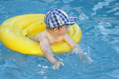 Child swim. In swimming pool with inflatable lifesaver in summer vacation royalty free stock image