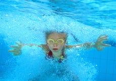 Child swim underwater in pool. stock image