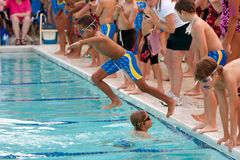 Child Swimmer Jumps Into Pool To Swim Relay Race Royalty Free Stock Image