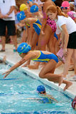 Child Swimmer Leaps Into Pool In Relay Race Stock Photos