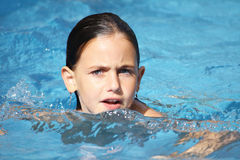 Child swimming. A caucasian child with blue eyes swimming in a pool Stock Image