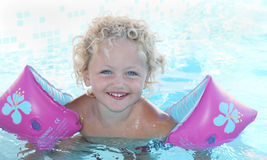Child swimming. A happy caucasian child with blonde hair and blue eyes swimming in a pool Royalty Free Stock Photography