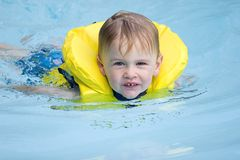 Child swimming. Boys in life jacket swims in pool royalty free stock photo