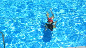 The child is swimming in the blue water of the pool. view from above. Girl dives under the water in the pool. The child is swimming in the blue water of the pool stock video