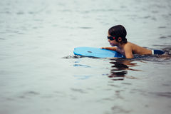 Child swimming on board in sea royalty free stock images