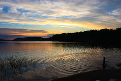 Child swimming in the evening lake Royalty Free Stock Photos