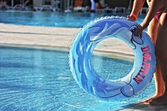 Baby swimming float. A child holding the blue swimming float ring by the edge of a pool Stock Image