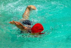 Child swimming freestyle. A young Caucasian child swimmer with blue swim wear and red cap swimming in the clear water of the swimming pool outdoors in summertime stock photos