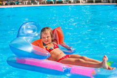 Child swimming on inflatable beach mattress. Little girl swimming on inflatable beach mattress. Armbands on hand Stock Images