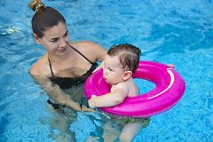 Cute little boy learning to swim with mother in pool. Child swimming lesson. Cute little boy learning to swim with mother in pool royalty free stock images