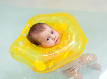Child swimming with neck swim ring Stock Photo