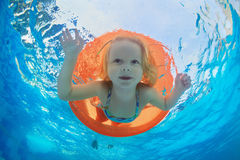 Child swimming on orange inflatable tube in pool Royalty Free Stock Photography