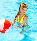 Child swimming in pool. Little girl playing ball in swimming pool Royalty Free Stock Photo