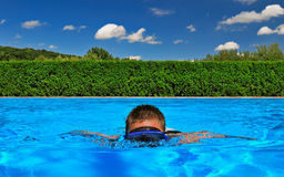 Child swimming in pool. Young boy wearing diving mask swimming in pool Stock Photo