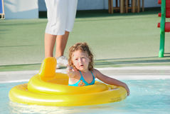 Child in swimming pool. Cute girl playing in yellow swimming pool inflatable Royalty Free Stock Images
